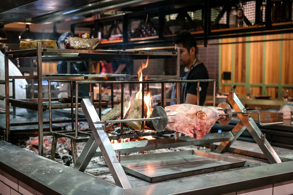 unique London restaurants: the open kitchen with a huge fire pit for roasting meats at Temper in SoHo